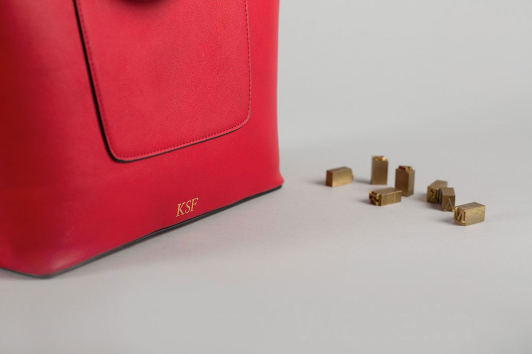 red personalised hot foil embossed handbag beside letterpress stamps